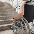 Elderly lady in wheelchair looking up stairs — Stockfoto