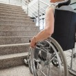 Elderly lady in wheelchair looking up stairs — Stock Photo