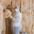 Worker filling walls with insulation - Stock Photo