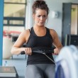 Exhausted woman training on row machine — Stock Photo #23054796