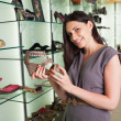 Woma holding shoe and smiling — Stock Photo #23054836