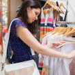 Woman with bag looking through clothes — Stock Photo #23054946