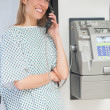 Happy patient using payphone — Stock Photo