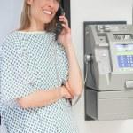 Happy patient using payphone — Stock Photo