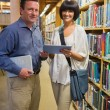 Man holding book standing next to woman using tablet pc — Foto Stock