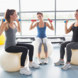 Three women lifting weights on exercise balls — Stock Photo