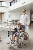 Child in neck brace being pushed in wheelchair by doctor — Stock Photo