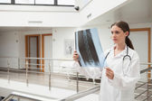 Female doctor analyzing x-ray at stairwell — Stock Photo