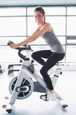 Smiling woman training on exercise bike — Stok fotoğraf