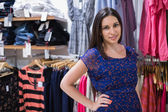 Woman in front of clothing display — Stock Photo