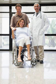 Pregnant woman in wheelchair, partner and doctor smiling — Stock Photo