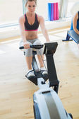Woman changing settings on row machine — Stock Photo