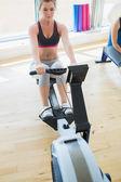Woman changing settings on row machine — Stock Photo