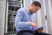 Hombre que usa la pc de la tableta junto servidores — Foto de Stock