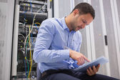 Man using tablet pc beside servers — Foto Stock