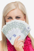 Beautiful blonde holding 100 euros banknotes — Stock Photo