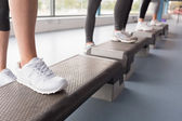 Womens feet stepping in aerobics class — Stock Photo