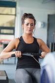 Woman training hard on row machine — Stock Photo