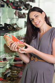 Woman holding a shoe — Stock Photo