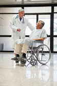 Doctor talking to a man in a wheelchair — Stock Photo