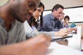 Studenten in einer vorlesung mit einer frau nachschlagen — Stockfoto