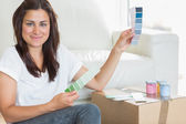 Woman happily choosing paint colours — Stock Photo