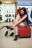 Woman sitting trying on shoes — Stock Photo