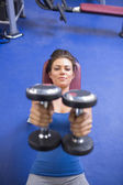 Woman straining to lift weights — Stock Photo