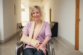 Patient in wheelchair with arm in sling — Stock Photo