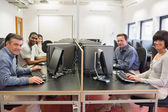 Grupo feliz en una sala de ordenadores — Foto de Stock