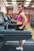 Smiling woman running on a treadmill in the gym — Stock Photo