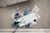 Tres enfermeras y un doctor empujando a un paciente en una cama — Foto de Stock