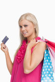 Blonde holding shopping bags and a card — Stock Photo