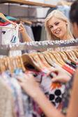 Mulher em pé atrás de um rack de roupas mostrando roupas — Foto Stock