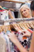 Woman standing behind a clothes rack showing clothes — ストック写真