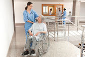 Nurse watching over old women sitting in wheelchair — Stock Photo