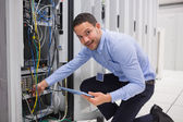 Smiling technician with tablet pc plugging cables into server — Stock Photo