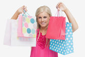 Happy blonde showing shopping bags — Stock Photo