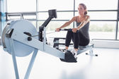 Woman training on row machine — 图库照片