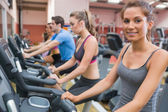 Smiling woman with other riding an exercise bike — Stock Photo