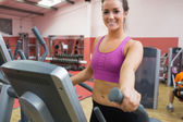 Smiling brunette stepping on a step machine — Stock Photo