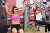 Women using weight machines — Stok fotoğraf