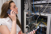 Woman working on servers with tablet pc on the phone — Photo