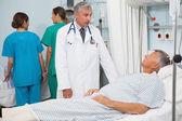Paciente acostado en la cama hablando con el doctor — Foto de Stock