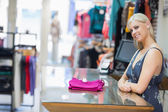 Woman smiling behind counter with folded clothes — Stock Photo