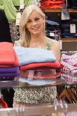 Mujer de pie en un estante de ropa sonriendo — Foto de Stock