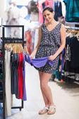 Mujer sonriendo y mirando ropa — Foto de Stock