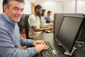 Smiling man sitting in front of the computer — Stock Photo
