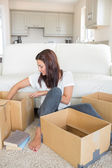 Woman happily unpacking moving boxes — Stock Photo