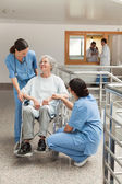 Old woman in wheelchair talking with nurses — Stock Photo